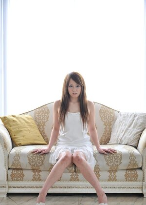 Sweet girl from Japan in white dress prefers to sit on white couch