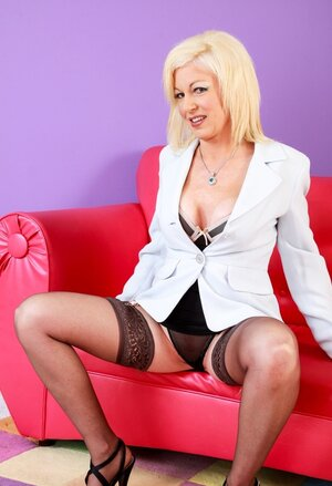 Mature blonde Sindi Star demonstrates her good-looking body on the sizeable red sofa