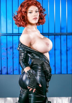Red-haired cutie pie poses in latex outfit that can hardly hide her huge jugs