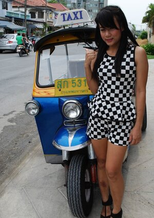 Inviting Thai adult model in a checkered dress gets into the Tuk Tuk Taxi