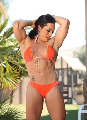 Diva in orange bikini has large biceps and masculine chest to disport fans