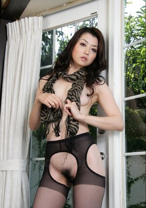 Exotic performer poses in sexy black pantyhose that expose her hirsute honey pot