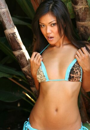Fragile Oriental girl becomes closer to nature by removing her sexy bikini