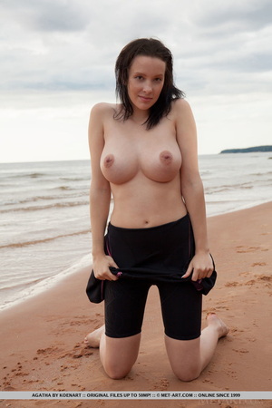 Brunette flashes fantastic tits and lays down on red beach to spread long legs